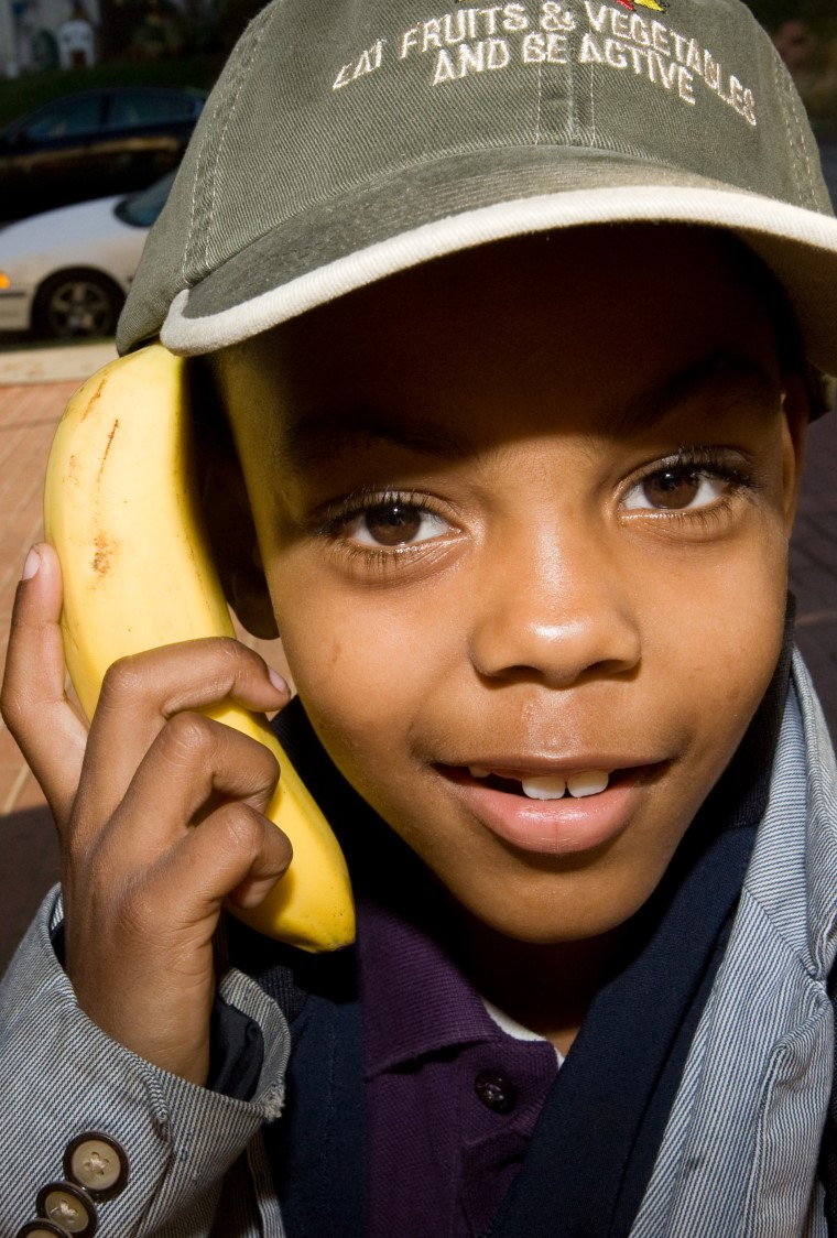 young boy using banana as a telephone