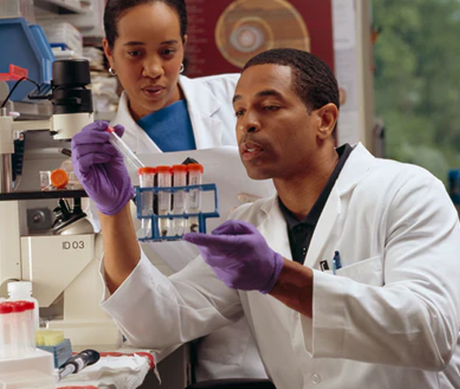 A male researcher checks test tubes as a female cancer researcher looks