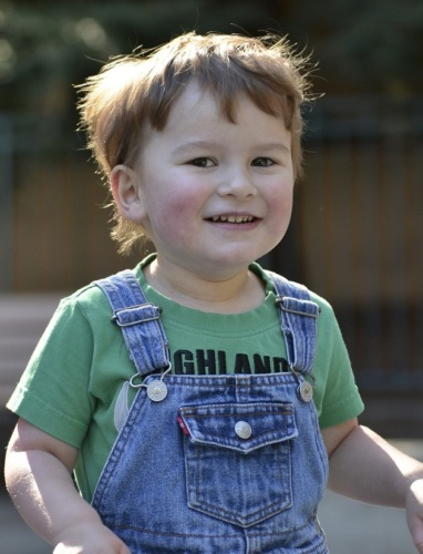 Child in overalls and green t-shirt, smiling at camera