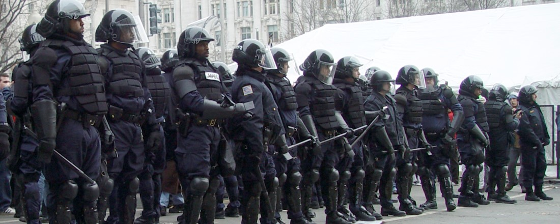 police officers dressed in riot gear standing in a line