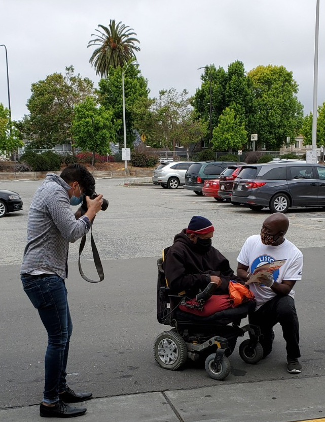A photographer takes a photo of a Listos California worker showing resources to a person in a wheelchair