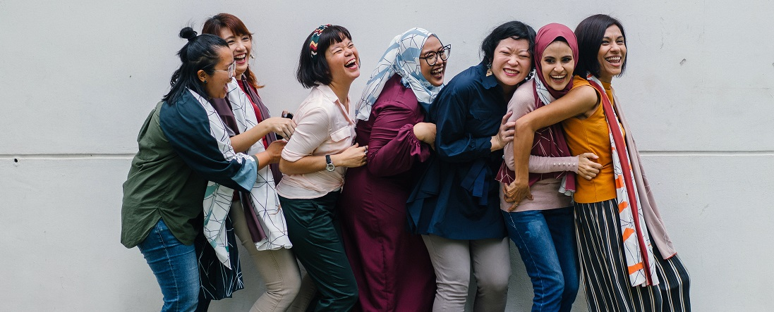 Women laughing in a row in front of a gray wall